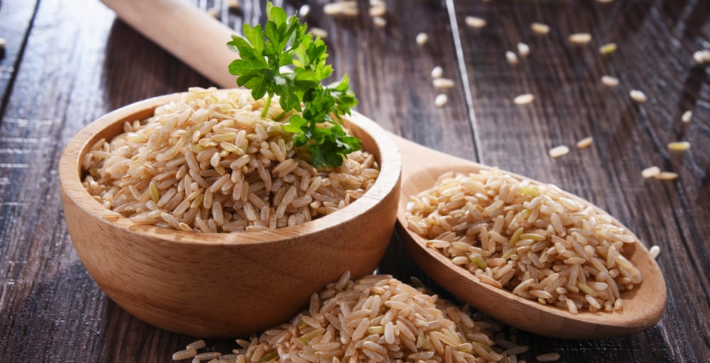 Bowl of brown rice on wooden table