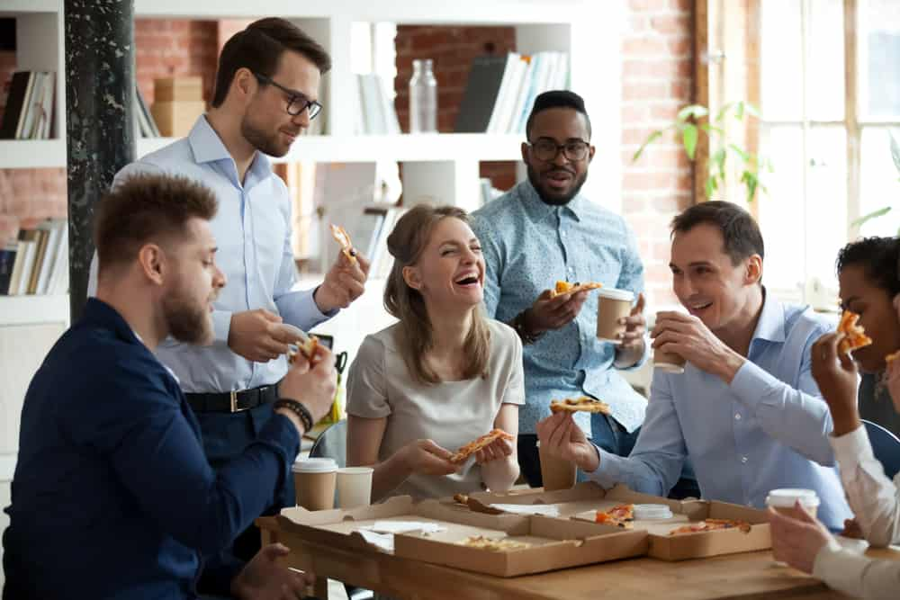 Co-workers talking and laughing while eating pizza at office 1