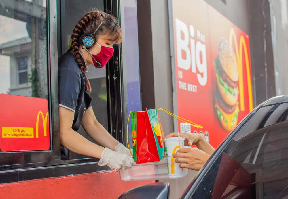 Female staff at McDonald's delivers food to customers