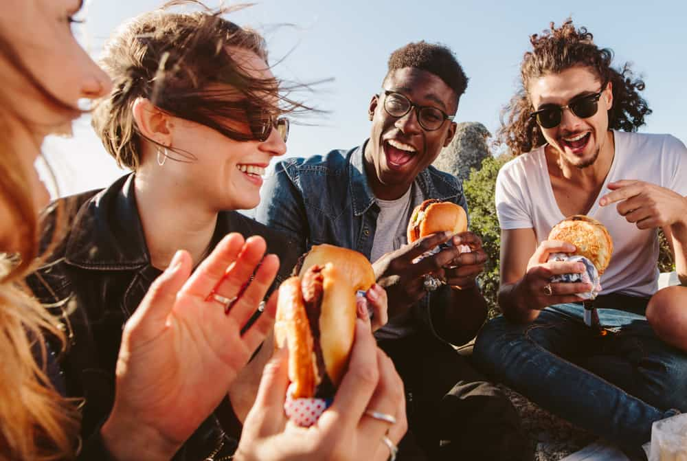Group of friends sitting, eating burgers