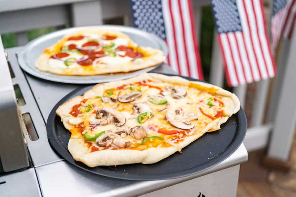 Preparing individual grilled pizzas on an outdoor gas grill