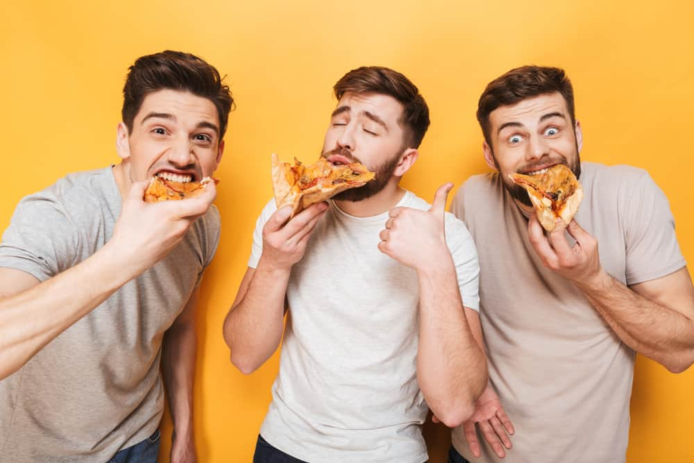 Three guys eating pizza isolated over yellow background