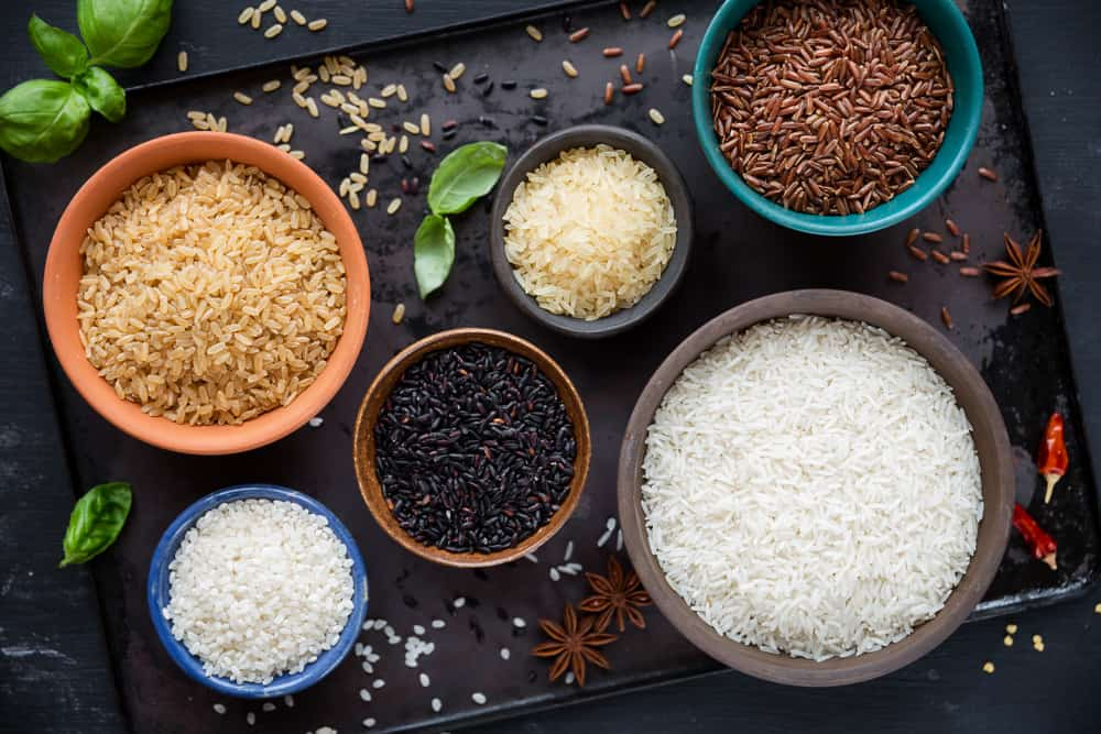 Variety of types and colours of rice - red, black, basmati, whole grain, long grain parboiled and arborio - in bowls