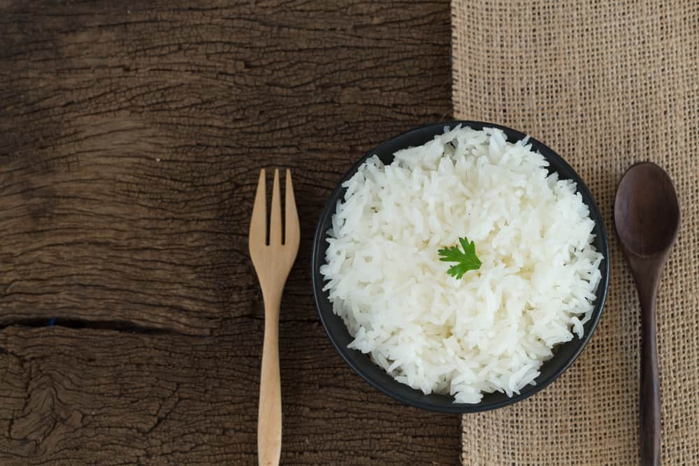 White rice in bowl on wooden Background