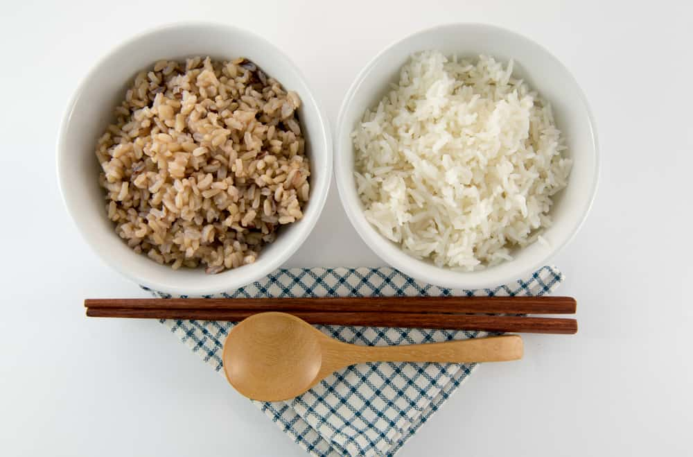Cooked brown and white rice on white background