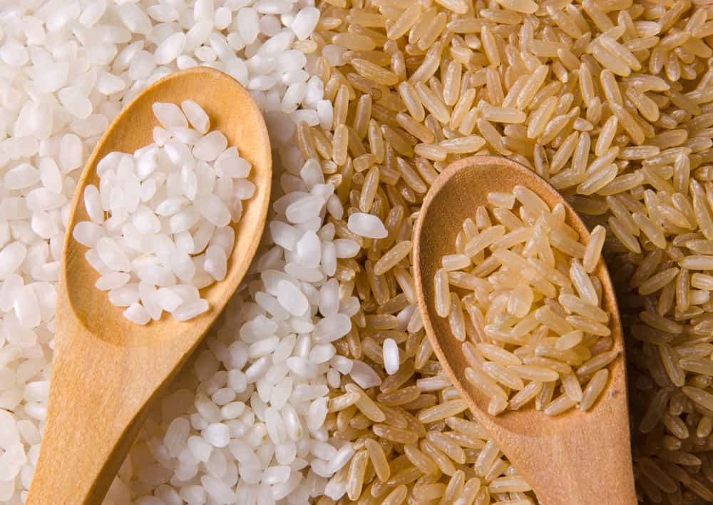 Natural white and brown long rice in wood spoons