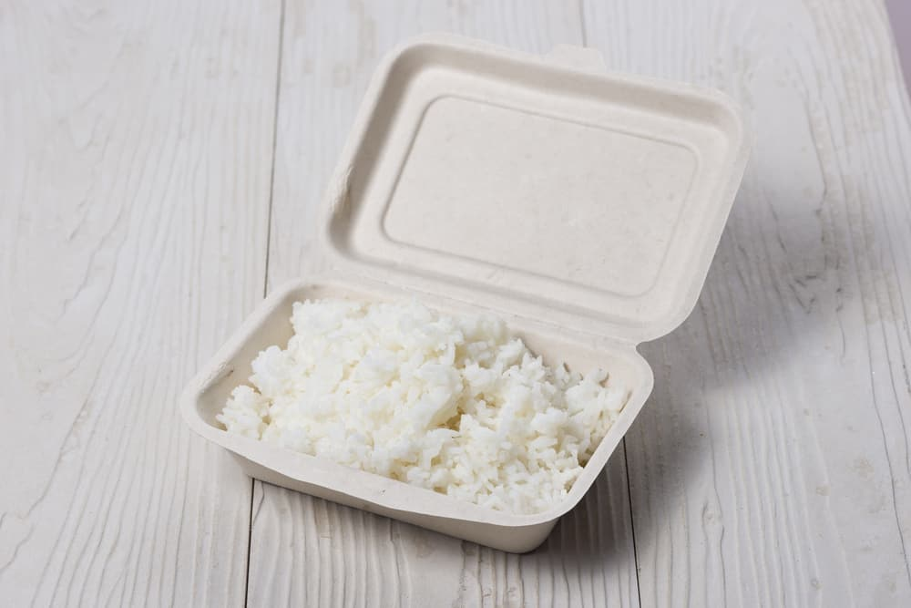 Take away rice in a paper box on wooden table